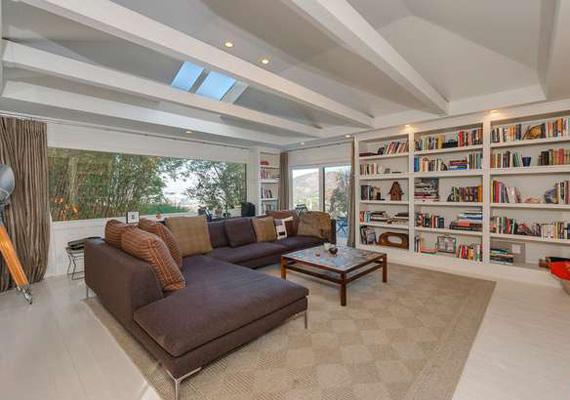 A ház óriási ablakai biztosítják a természetes fényt, és a környező fák és növények üde háttérként szolgálnak a nehéz bőr ülőalkalmatosságokhoz.