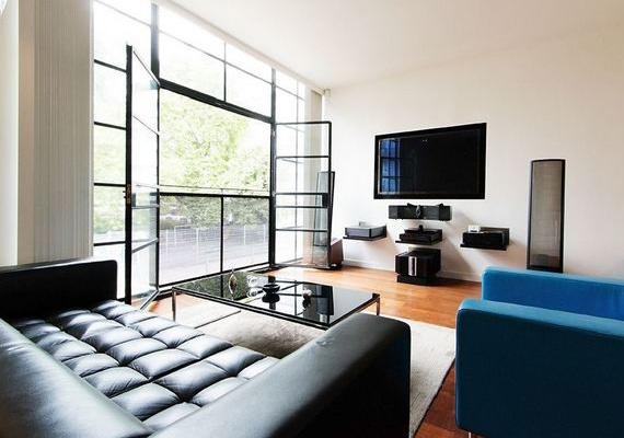 A nappaliban hatalmas bőrkanapén elterülve lehet bámulni a televíziót. A méretes ablakok rengeteg fényt engednek be a térbe.