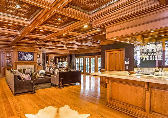 A földszinti nappali igazi klasszikus hatást kelt a fa burkolóelemeknek és bőrbútoroknak köszönhetően. A bárpultban rengeteg ital áll a vendégek rendelkezésére.