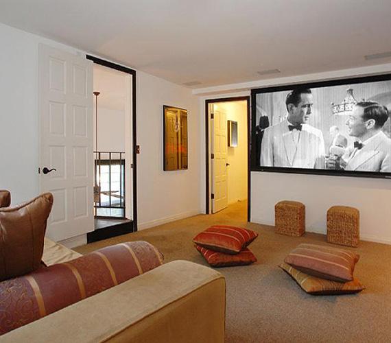 Az egyik helyiség házimoziként funkcionál, a kényelemről a hatalmas bőrkanapé, a szórakoztatásról pedig az egyik falat szinte teljes egészében elfoglaló képernyő gondoskodik.