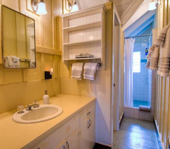 A fürdőszoba vaníliasárga berendezése meleg hangulatot áraszt, a lakók zuhanyfülkében tisztálkodhatnak.