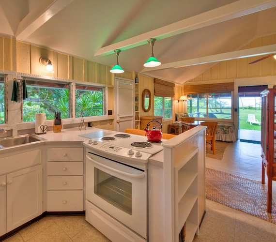 A vendégház nappalija és konyhája egy légtérben található, a nyitott erkélyajtón pedig egyenesen a sok zöldre és az óceánra látni.