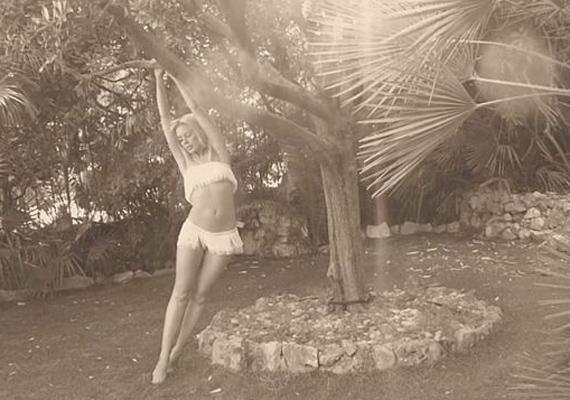 Kylie igazán vadítóan pózol a fának támaszkodva, rojtos, fehér bikinijében. Habár a sztár már közel jár az 50-hez, teste még mindig elképesztően feszes.