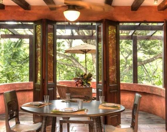 Az étkező hatalmas ablakai a dzsungel dús növényzetére néznek.