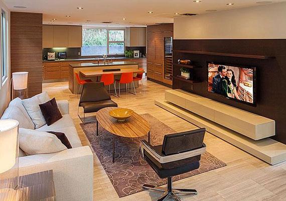 A háznak hatalmas nappalija van, a fehér bőrüléses kanapéról pedig kényelmesen lehet tévézni. A hatalmas helyiség egybe nyílik a konyhával.
