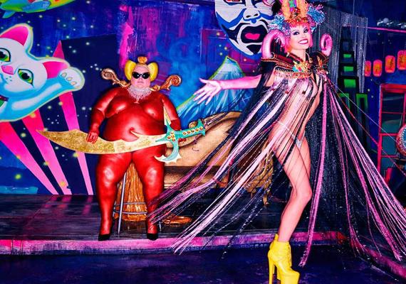 Nem igazán értjük a koncepciót, de elég érdekes beállítás. A piros, ördögnek öltözött, latexruhás, kövér férfi egy karddal a kezében nézegeti a karneváli jelmezbe öltözött Pamet.