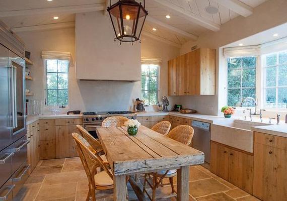A konyha központi helyén egy rusztikus faasztal áll, ahol kényelmesen étkezhetnek a lakók.